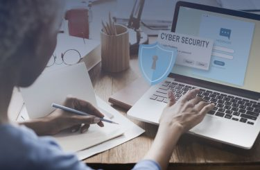 woman working on computer with cyber security graphic overlay